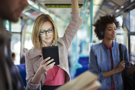 Businesswoman using digital tablet on train - CAIF14558