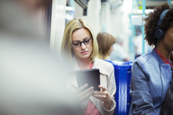 Businesswoman using digital tablet on train - CAIF14561