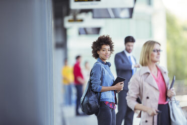 Woman holding digital tablet and waiting for train in station - CAIF14564