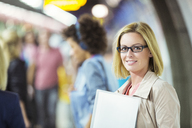 Businesswoman smiling in train station - CAIF14594