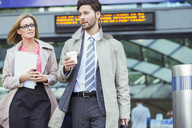 Business people walking and talking in train station - CAIF14600