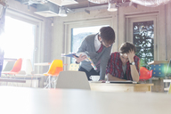 Creative businessmen reviewing document edits in sunny office - CAIF14624