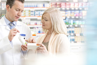 Pharmacist discussing prescription with customer in pharmacy - CAIF14678