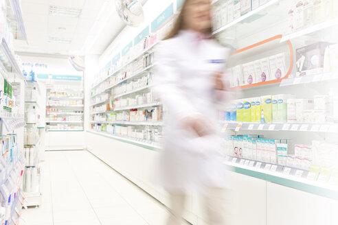 Pharmacist walking in aisle of pharmacy - CAIF14702