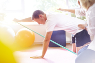 Physical therapist guiding man pulling resistance band - CAIF14753
