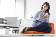 Smiling businesswoman texting with cell phone on cushion in office - CAIF14759