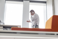 Businessman talking on cell phone gesturing at office window - CAIF14762