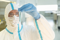 Scientist in clean suit examining sample in test tube in laboratory - CAIF14795