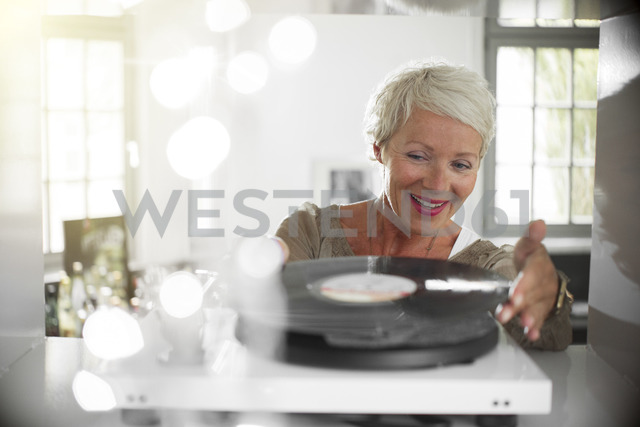 Older woman playing vinyl record on turntable - CAIF14798