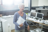 Businesswoman carrying paperwork in office - CAIF14804