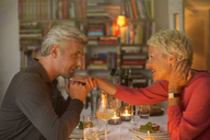 Older man kissing hand of wife at romantic dinner - CAIF14813