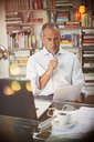 Businessman reading paperwork at home office desk - CAIF14822