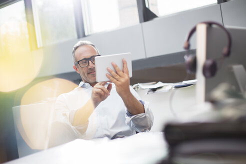 Businessman using digital tablet at office desk - CAIF14828