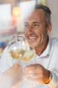 Smiling older man toasting with white wine - CAIF14834