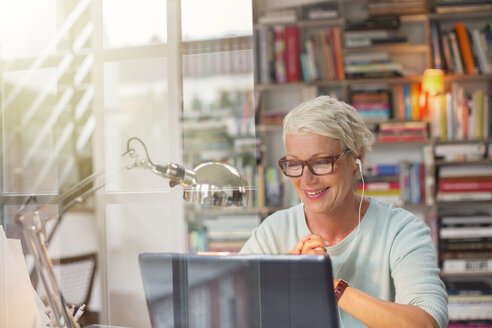 Businesswoman listening to earbuds and working in home office - CAIF14840