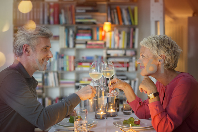 Older couple toasting each other at romantic dinner - CAIF14855