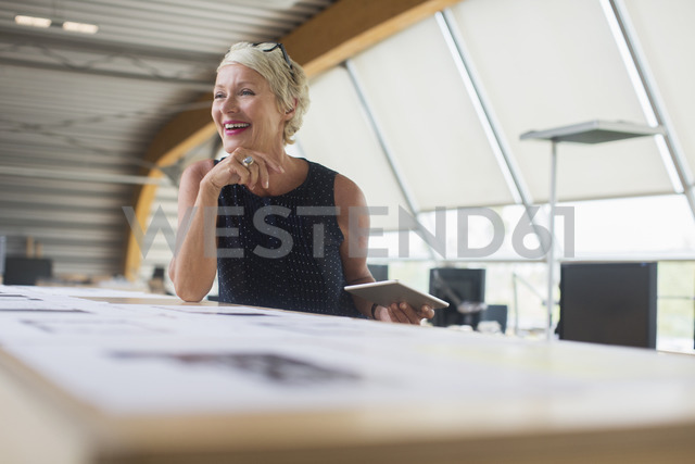Businesswoman using digital tablet in office - CAIF14870