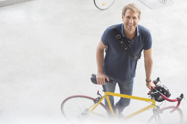 Smiling man standing with bicycle - CAIF14948