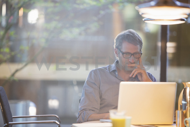 Businessman working on laptop in office - CAIF14951