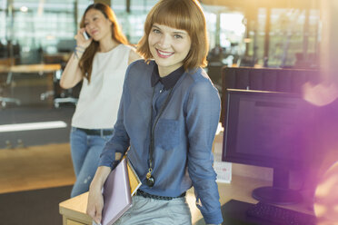 Businesswoman smiling in office - CAIF14963