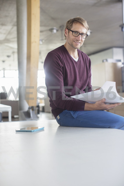 Businessman reading paperwork in office - CAIF14966