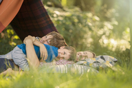 Father and sons relaxing together near camping tent - CAIF14981
