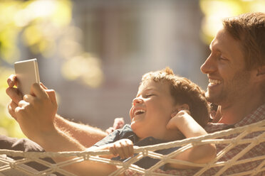 Father and son using digital tablet in hammock - CAIF14984