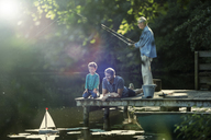 Boy fishing and playing with toy sailboat with father and grandfather at lake - CAIF14987