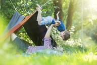 Father and son playing near camping tent - CAIF14993