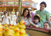 Parents with two children having fun with fishing game in amusement park - CAIF15011