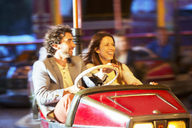 Couple on bumper car ride in amusement park - CAIF15014
