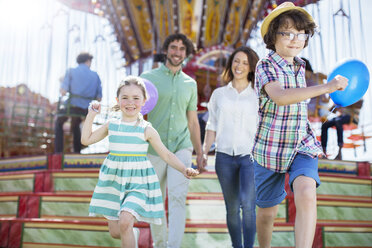 Children running in front of carousel, parents following them - CAIF15017