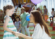 Mother and girl with balloon looking at each other in amusement park - CAIF15023