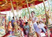 Woman sitting on horse on carousel in amusement park - CAIF15029