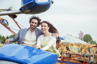 Couple enjoying ride on carousel in amusement park - CAIF15032