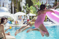Children jumping into resort swimming pool - CAIF15059