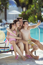 Family with two children taking selfie by swimming pool - CAIF15068