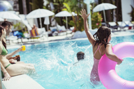 Girl with pink inflatable ring jumping into swimming pool, family in background - CAIF15074
