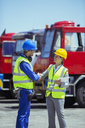 Businesswoman and worker shaking hands near trucks - CAIF15092