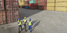 Businessmen and worker walking near cargo containers - CAIF15110