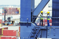Worker and businessman shaking hands on cargo crane - CAIF15128