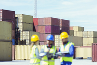 Businessman and workers talking near cargo containers - CAIF15131