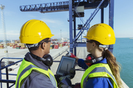 Workers using digital tablet on cargo crane - CAIF15134