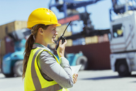 Businesswoman using walkie-talkie near cargo containers and trucks - CAIF15137