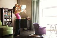 Happy woman lifting baby girl at home - CAVF06087