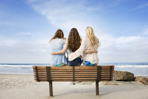 Rear view of friends sitting on bench at beach - CAVF06135
