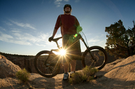 Low angle view of man with bicycle standing on mountain against sky - CAVF06186