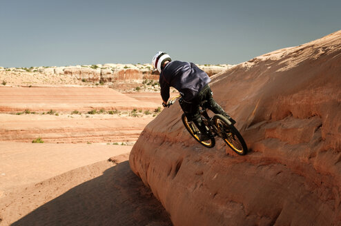 Rear view of man cycling on rock formation against clear sky - CAVF06189