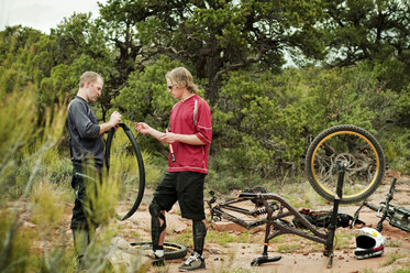 Friends repairing bicycle tire while standing on field - CAVF06195