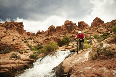 Mountain biker cycling on rocks by river against cloudy sky - CAVF06201